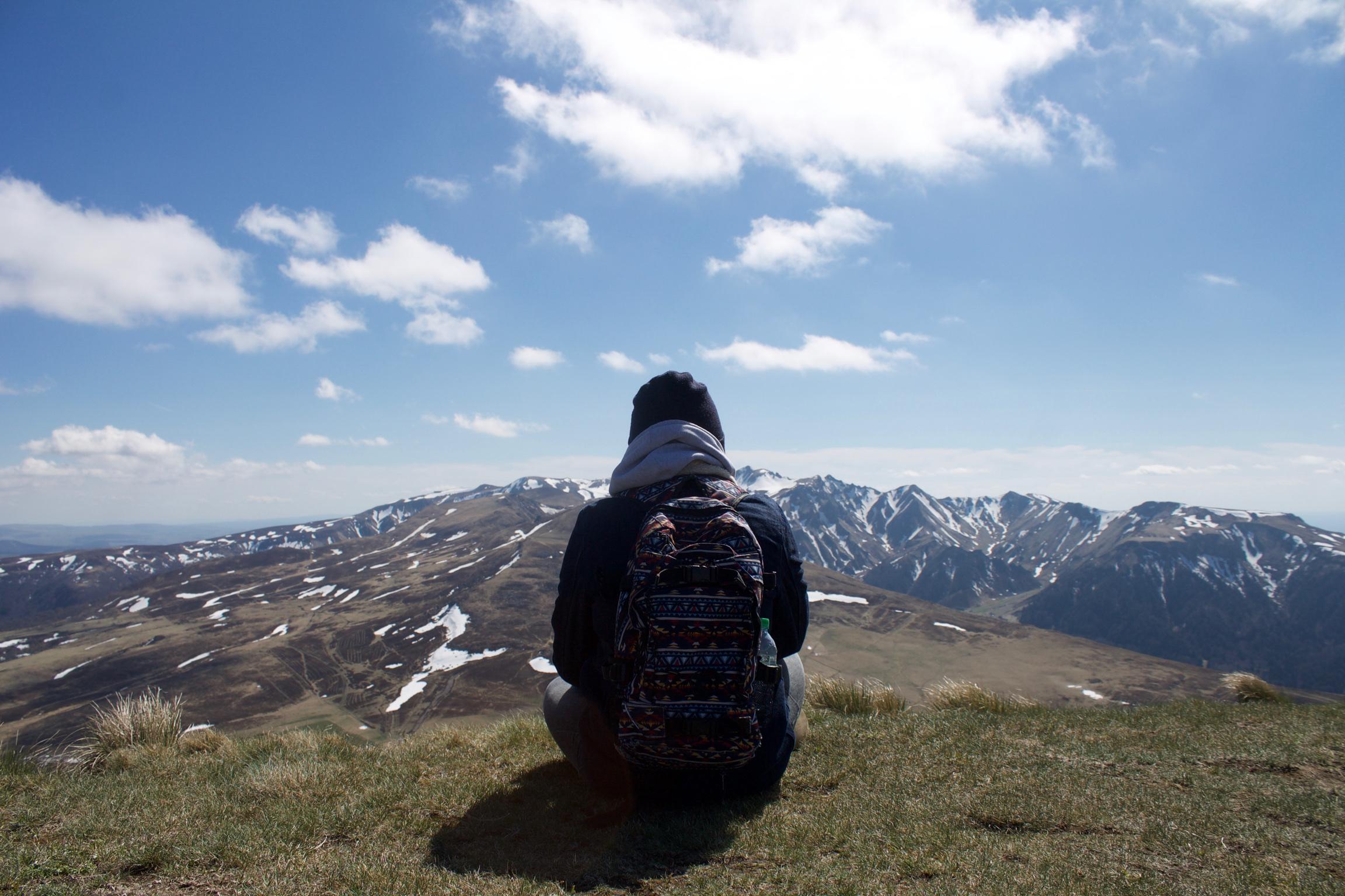 Un Homme chaudement vêtu assis au sommet du Col de la Croix Saint-Robert, faisant face aux monts Dores et au Puy de Sancy.
