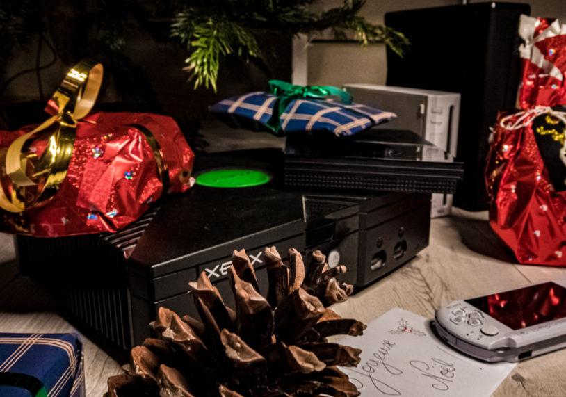 Photo de la première Microsoft Xbox Vanilla, de la Sony PlayStation Portale, de la Sony Playstation 2, de la Nintendo Wii ainsi que de la Microsoft Xbox 360 regroupés parmis d'autres cadeaux sous un sapin de Noël festivement décoré.